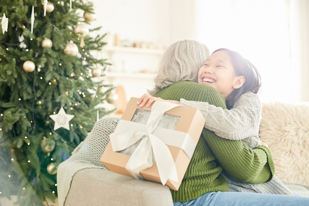 Gelukkig meisje dat haar moeder omhelst, dankt ze haar voor het kerstcadeau