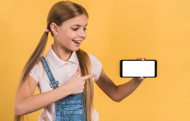 Gelukkig meisje dat iets op mobiele telefoon met witte het schermvertoning toont