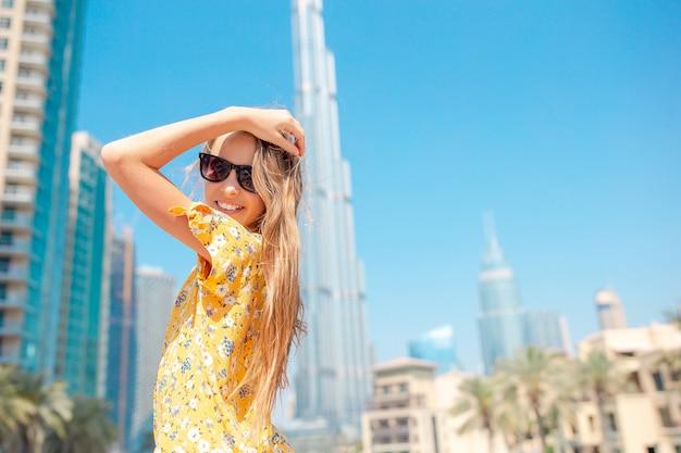 Gelukkig meisje dat in doubai met burj khalifa-wolkenkrabber op de achtergrond loopt.