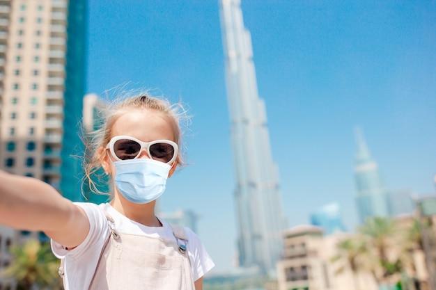 Gelukkig meisje dat in dubai met wolkenkrabbers loopt