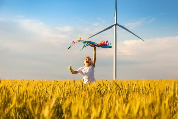 Gelukkig meisje dat in een tarweveld met een vlieger in de zomer loopt