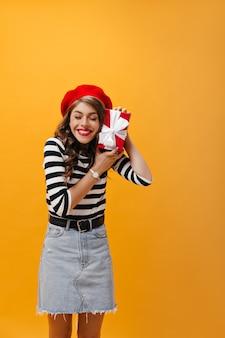Gelukkig meisje dat in gestreept overhemd en denimrok rode giftdoos houdt. blije jonge vrouw met golvend haar in moderne uitrusting met polshorloge het glimlachen.