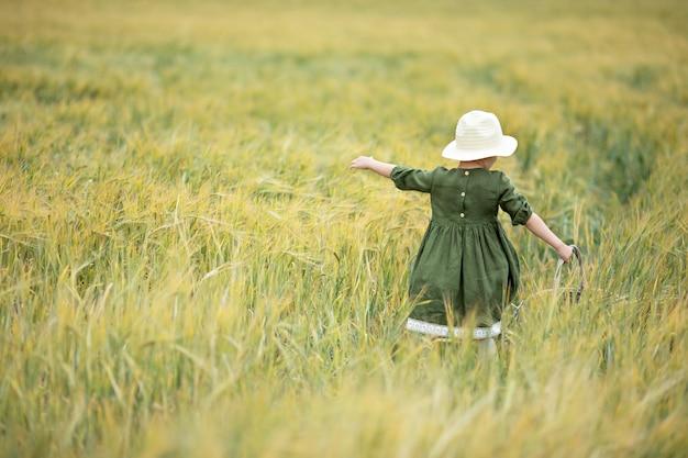 Gelukkig meisje dat in gouden tarwe loopt, die van het leven op het gebied geniet. natuurschoon en gebied van tarwe. familie buiten levensstijl. vrijheid concept. schattig klein meisje in zomer veld