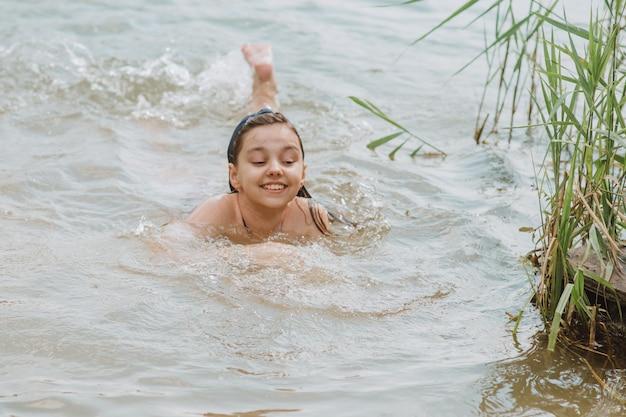 Gelukkig meisje dat in het meer zwemt. zomervakantie.