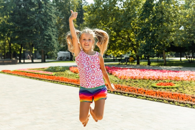 Gelukkig meisje dat in het park springt. klein meisje dat ijs eet en plezier heeft in de stad.