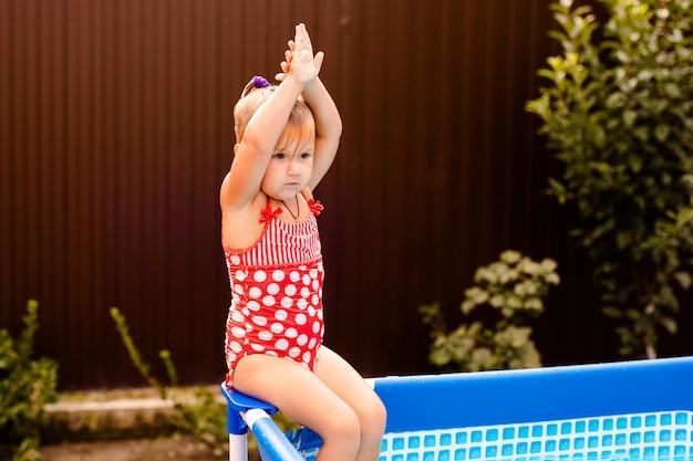 Gelukkig meisje dat in rood zwempak thuis in openlucht zwembad springt. babymeisje dat leert te zwemmen. waterplezier voor kinderen.