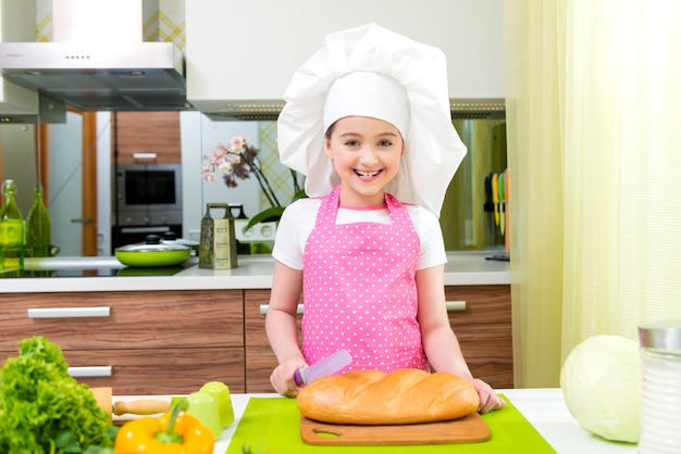 Gelukkig meisje dat in roze schort brood in de keuken snijdt.