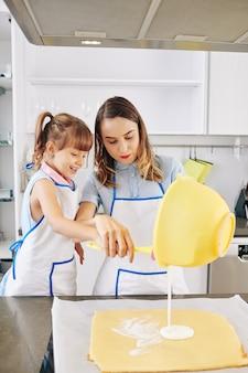 Gelukkig meisje dat in schort moeder helpt om roomglazuur op cake te zetten die zij samen bakten