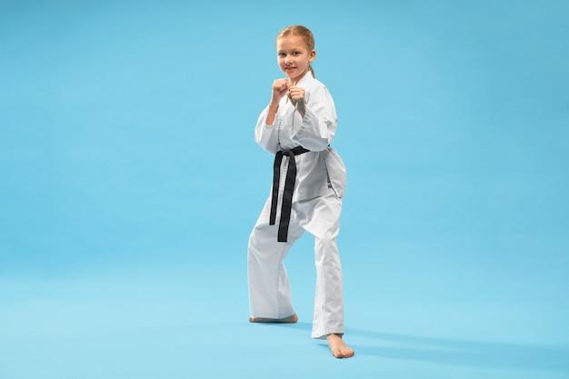 Gelukkig meisje dat in witte kimono camera bekijkt terwijl opleiding