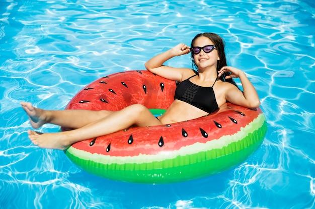 Gelukkig meisje dat in zwembad drijft