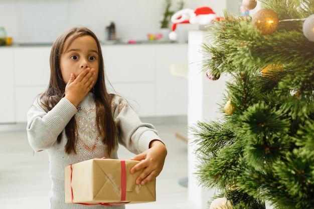 Gelukkig meisje dat kerstpyjama's draagt die bij een open haard in een comfortabele donkere woonkamer op kerstavond spelen. thuis vieren van kerstmis.