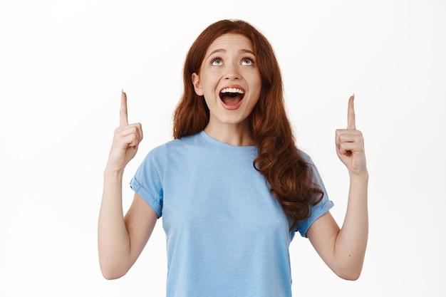 Gelukkig meisje dat lacht en met de vingers omhoog wijst, terwijl ze casual kleding op wit draagt