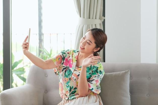 Gelukkig meisje dat met de hand zwaait met smartphone-app die geniet van online virtueel chat-videogesprek met vrienden