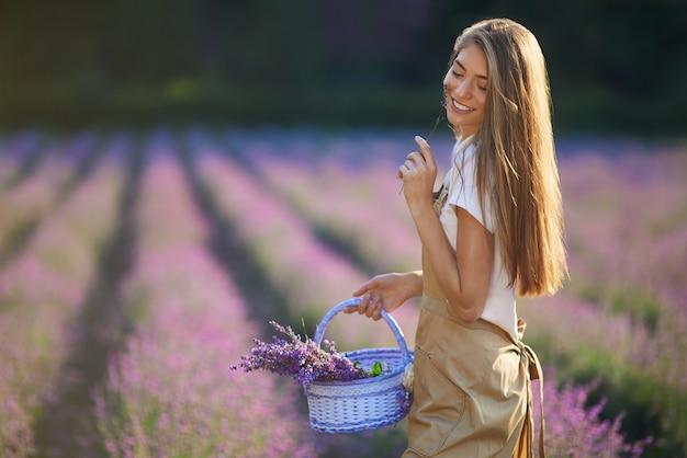 Gelukkig meisje dat met lavendelpatches in de mand loopt