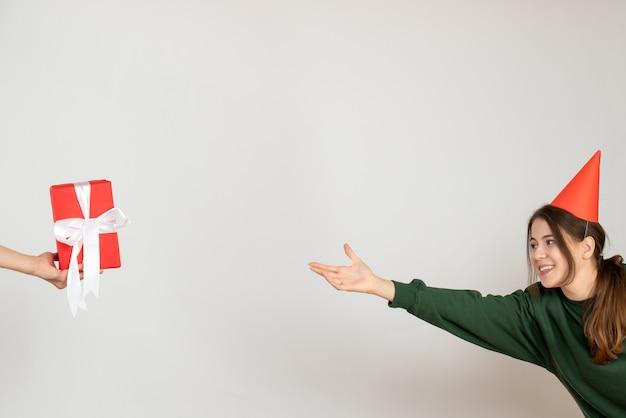 Gelukkig meisje dat met partij glb gift in menselijke hand op wit probeert te vangen