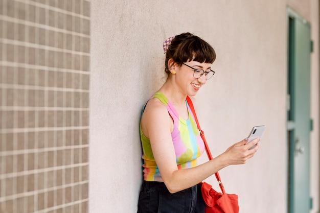 Gelukkig meisje dat mobiele telefoon controleert op berichten