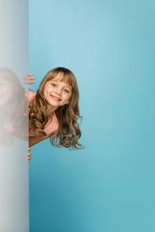 Gelukkig meisje dat op blauwe studiomuur wordt geïsoleerd