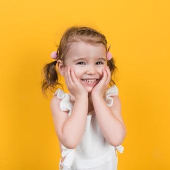 Gelukkig meisje dat op gele achtergrond glimlacht