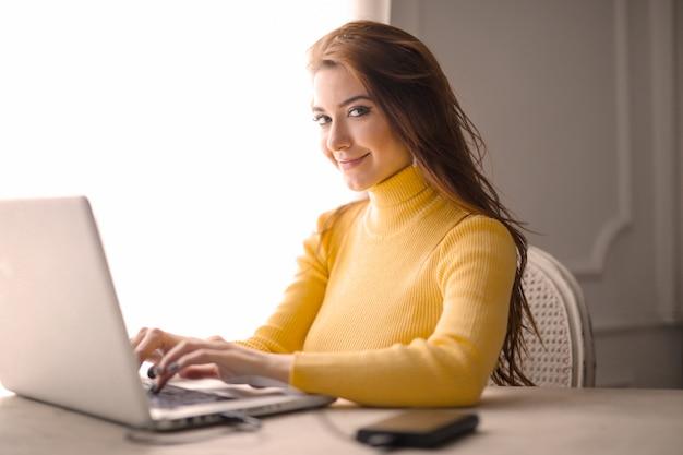 Gelukkig meisje dat op laptop werkt