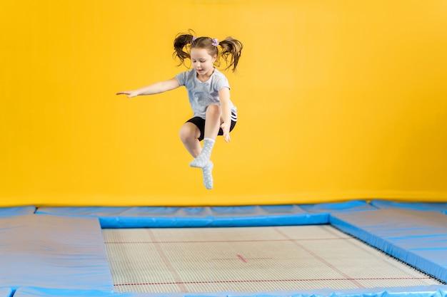 Gelukkig meisje dat op trampoline in geschiktheidscentrum springt