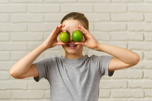 Gelukkig meisje dat pret heeft en haar ogen bedekt met limoen, gezond eten, biologisch voedsel, fruitdieet, concept
