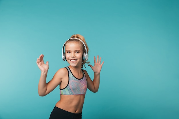 Gelukkig meisje dat sportkleding draagt die aan muziek met hoofdtelefoons luistert die over blauwe muur wordt geïsoleerd