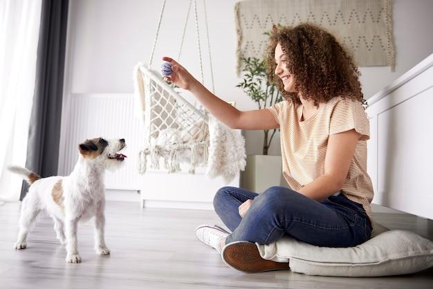 Gelukkig meisje dat thuis met haar hond speelt