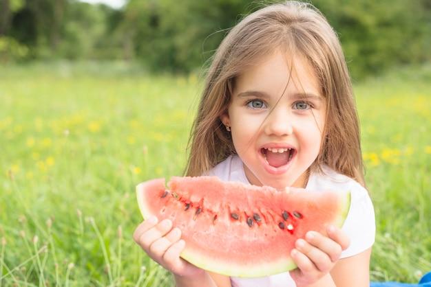 Gelukkig meisje dat van watermeloen in het park geniet