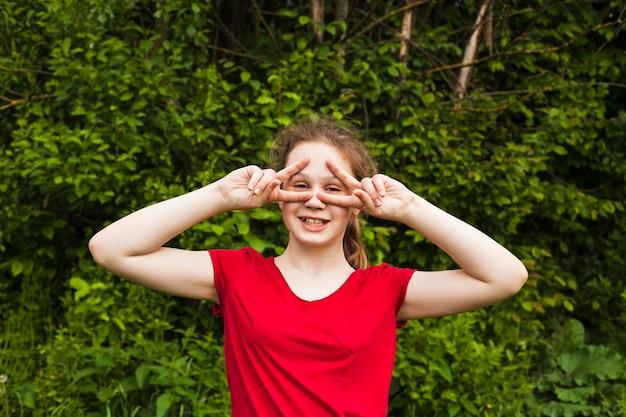 Gelukkig meisje dat zich in park bevindt en door v-teken kijkt