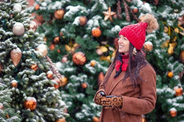 Gelukkig meisje dichtbij sparrentak in sneeuw voor nieuw jaar.