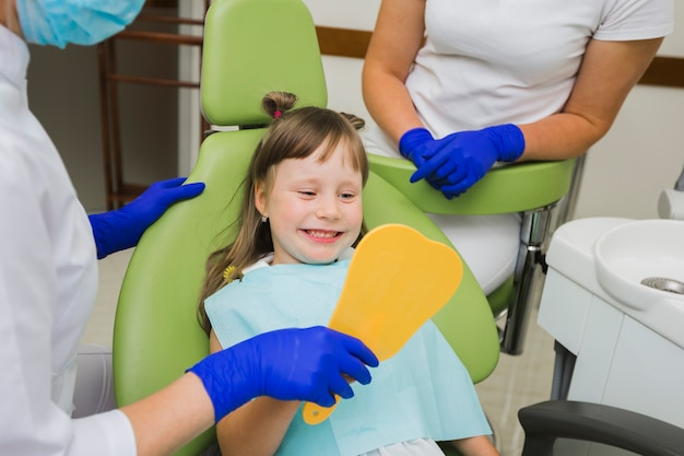 Gelukkig meisje die bij tandarts in de spiegel kijken
