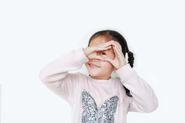 Gelukkig meisje die driehoek met geïsoleerd het kijken door haar handen maken.