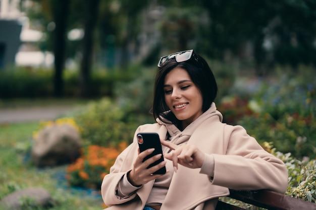 Gelukkig meisje die een slimme telefoon in een stadsparkzitting op een bank met behulp van
