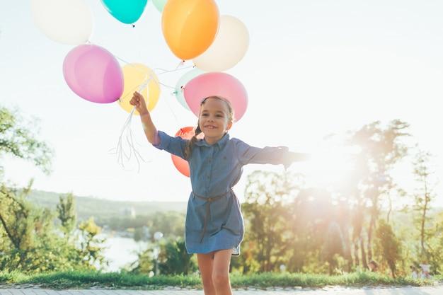 Gelukkig meisje die kleurrijke ballons in het stadspark houden