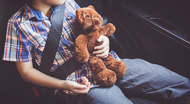 Gelukkig meisje die veiligheidsgordels in auto dragen