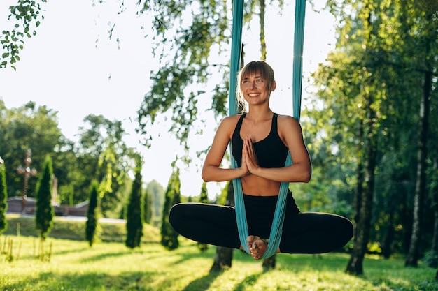 Gelukkig meisje doet yoga vliegen buiten gemaakt lotus houding. jonge yoga maakt reclame tijdens het sporten.