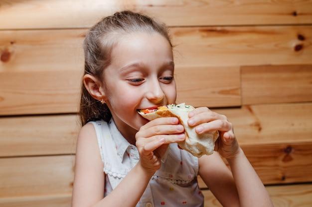 Gelukkig meisje eet vegetarische wrap ijsberg