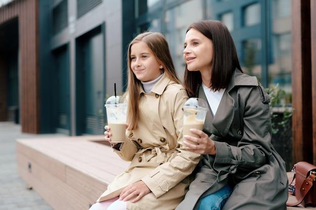 Gelukkig meisje en haar moeder in trenchcoats met melkcocktails terwijl u ontspant in de stedelijke omgeving