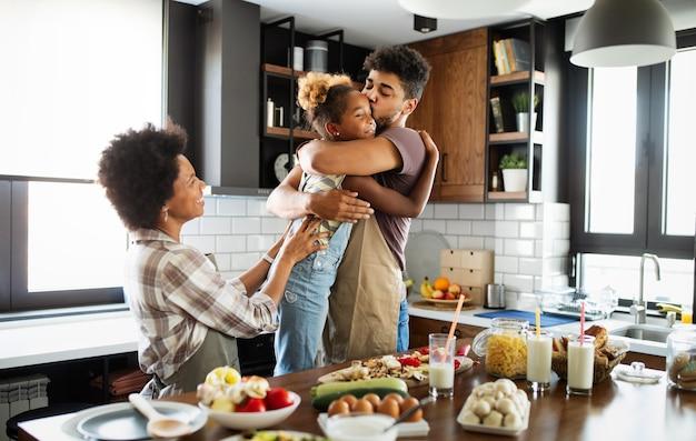 Gelukkig meisje en haar mooie ouders glimlachen terwijl ze thuis in de keuken koken