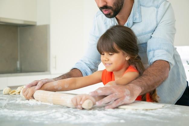 Gelukkig meisje en haar vader die deeg op keukentafel met slordige bloem rollen.