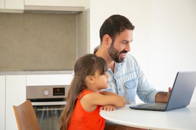 Gelukkig meisje en haar vader met behulp van laptop voor video-oproep, aan tafel zitten, kijken naar display en glimlachen.