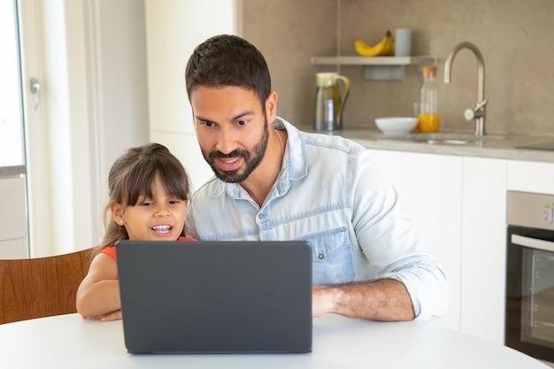 Gelukkig meisje en haar vader met behulp van laptop, zittend aan tafel, film kijken, display kijken.