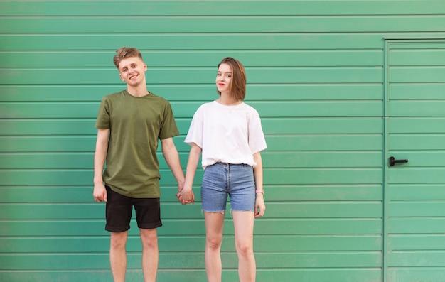 Gelukkig meisje en jongen zijn geïsoleerd op de achtergrond van een groene muur