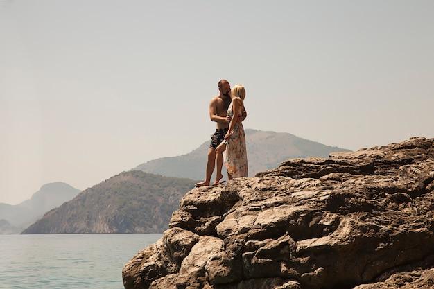 Gelukkig meisje en man in strandkleren kussen op kustklif tegen de achtergrond van de blauwe oceaanzee en de rotsachtige bergen