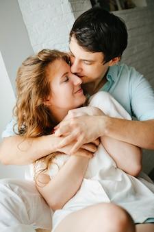 Gelukkig meisje en man knuffelen in de buurt van venster in huis. witte en blauwe kleding. valentijnsdag.