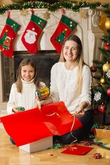 Gelukkig meisje en moeder zitten bij de open haard en kerstcadeautjes inpakken