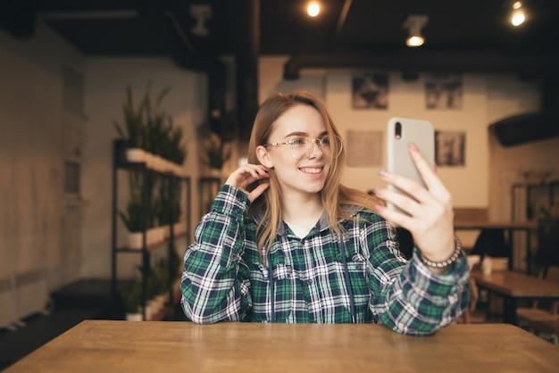 Gelukkig meisje gebruikt een smartphone in een gezellig café, kijkt naar de telefoon en glimlacht