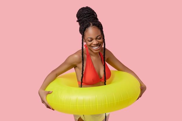 Gelukkig meisje. genoten van een afro-amerikaanse vrouw die een gele buis vasthoudt en er gelukkig uitziet