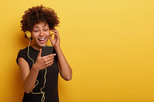 Gelukkig meisje gericht in mobiele telefoon, geniet van het luisteren naar muziek, graag afspeellijst vernieuwen, speciale app gebruikt, breed glimlacht