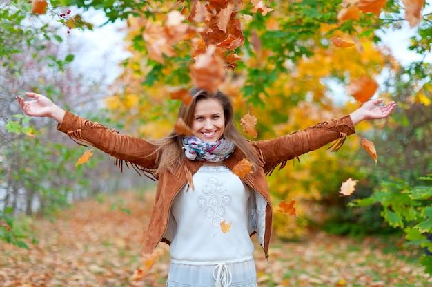 Gelukkig meisje gooit esdoornbladeren